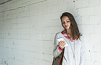 Young woman leaning against brick wall looking at cell phone - UUF006194
