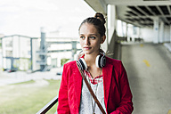 Young woman with headphones in parking garage - UUF006197