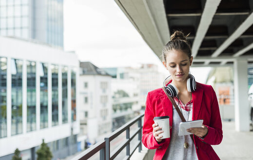 Young woman with coffee to go, headphones and phablet in parking garage - UUF006200