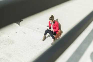 Young woman with coffee to go, headphones and phablet sitting at concrete wall - UUF006203