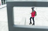 Young woman with cell phone and inline skates on parking level - UUF006206