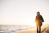 Young woman walking on the beach in winter - JRFF000240