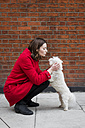 UK, London, young woman crouching on pavement face to face to her dog - MAUF000147
