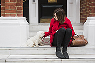 UK, London, young woman sitting on stairs besides her dog - MAUF000150
