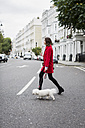 UK, London, young woman wearing red jacket crossing the street with her dog - MAUF000153