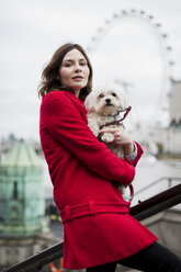 UK, London, portrait of young woman with dog on her arms and London Eye in the background - MAUF000156
