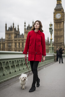 Young woman wearing red jacket going walkies with her dog - MAUF000159