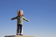 Spain, Consuegra, happy little girl standing on summit with arms outstretched - ERLF000089