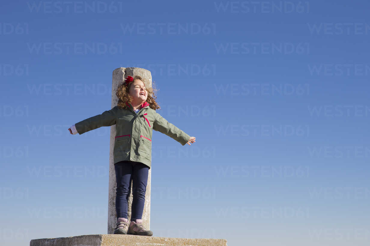 Spain, Consuegra, happy little girl standing on summit with arms outstretched - ERLF000089 - Enrique Ramos/Westend61