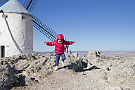 Spain, Consuegra, jumping little girl with windmill in the background - ERLF000092