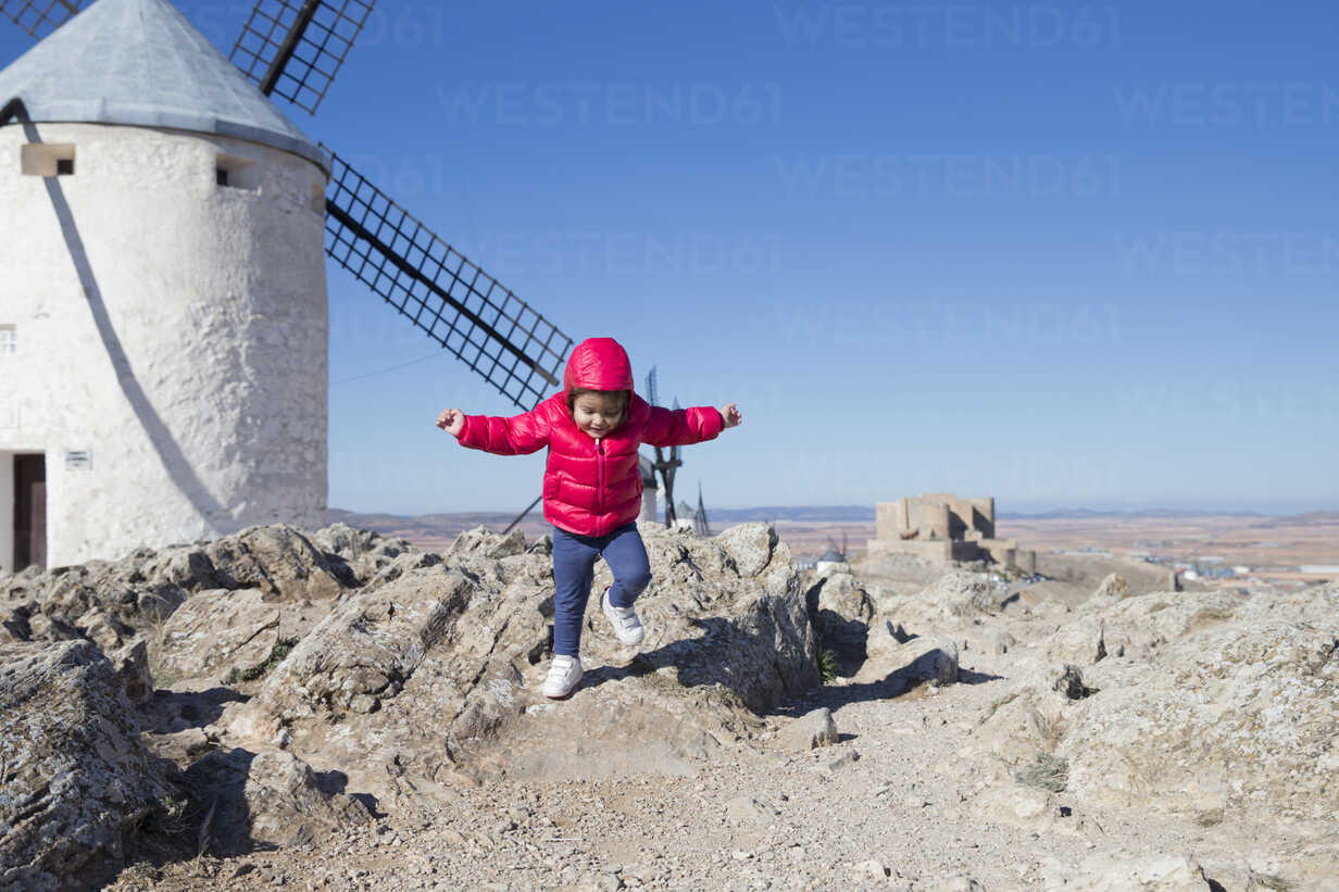 Spain, Consuegra, jumping little girl with windmill in the background - ERLF000092 - Enrique Ramos/Westend61
