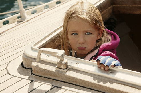Girl looking out of cabin of sailing boat pouting - TMF000081