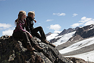 Italy, South Tyrol, Schnalstal, boy and girl sitting on mountain peak - TMF000084