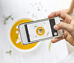 Woman taking a photo of carrot pumpkin soup with her smartphone, close-up - KNTF000210