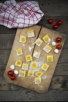 Homemade noodles, ravioli, filled with tomato mozzarella on chopping board - LVF004311
