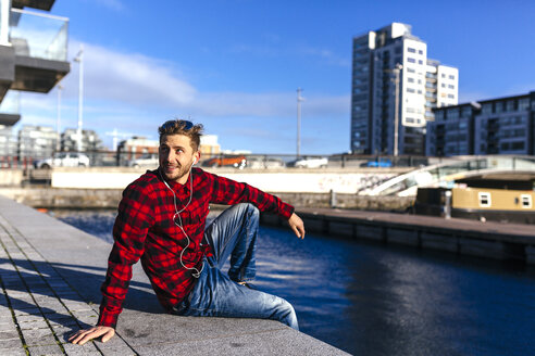 Ireland, Dublin, young man at city dock listening to music - BOYF000047