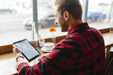 Man in a coffee shop looking at digital tablet - BOYF000053