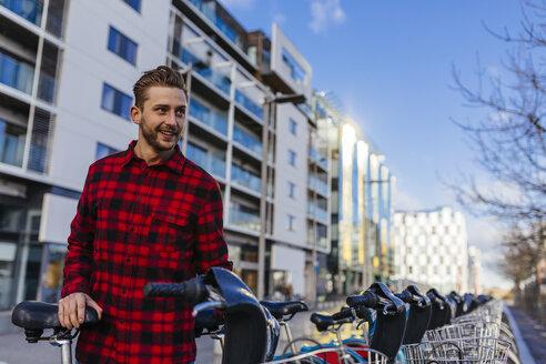 Ireland, Dublin, smiling young man with city bike - BOYF000056