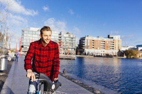 Ireland, Dublin, young man at city dock with city bike - BOYF000059