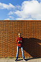 Young man at brick wall using a cell phone - BOYF000062