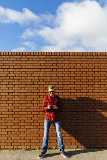 Young man at brick wall using a cell phone - BOYF000062