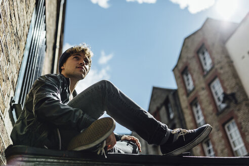 Ireland, Dublin, young man sitting on the ground of an alley - BOYF000067