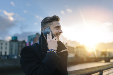Ireland, Dublin, smiling young businessman telephoning with smartphone at backlight - BOYF000079