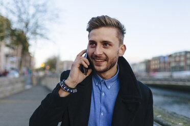 Ireland, Dublin, portrait of young businessman telephoning with smartphone - BOYF000082
