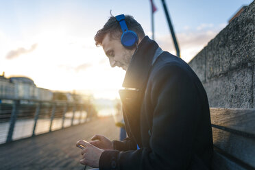 Ireland, Dublin, young man sitting on a bench at backlight hearing music with headphones - BOYF000085