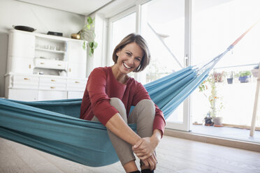 Happy woman at home sitting in hammock - RBF003571