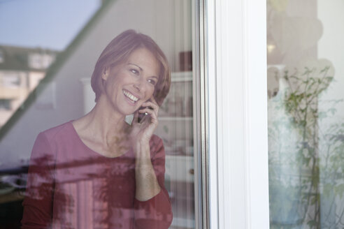 Smiling woman on the phone at the window - RBF003574