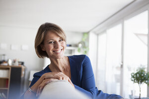 Portrait of smiling woman at home sitting on couch - RBF003577
