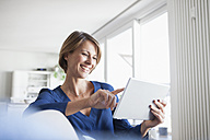 Smiling woman at home sitting on couch using digital tablet - RBF003580