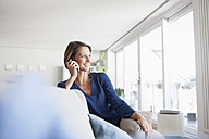 Smiling woman at home on the phone - RBF003583