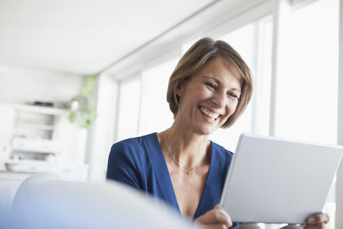 Smiling woman at home using digital tablet - RBF003592