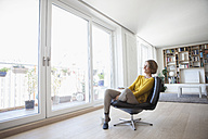 Relaxed woman at home sitting on leather chair - RBF003598