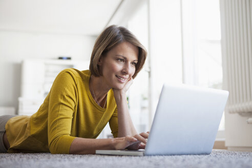 Relaxed woman at home lying on floor using laptop - RBF003610