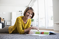 Relaxed woman at home lying on floor reading magazine - RBF003613