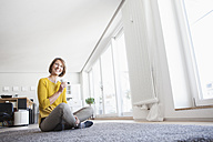 Relaxed woman at home sitting on floor holding cup - RBF003616
