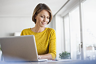 Smiling woman at home using laptop - RBF003622