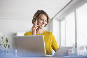 Smiling woman at home with laptop, digital tablet and cell phone - RBF003625