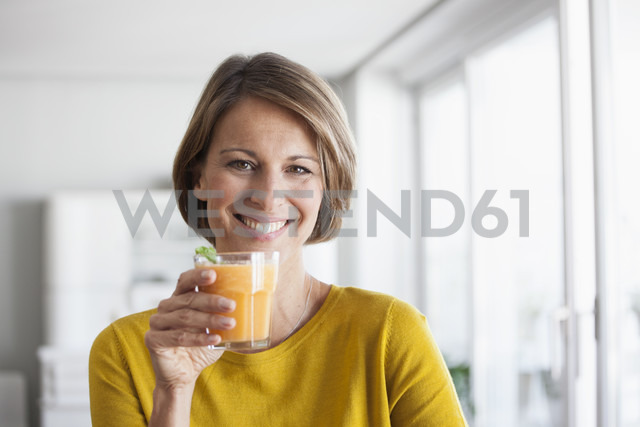 Portrait of smiling woman with a smoothie - RBF003631