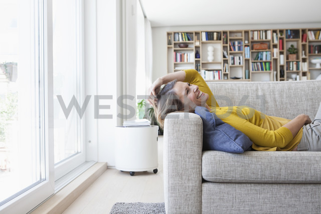 Happy woman at home lying on couch - RBF003634