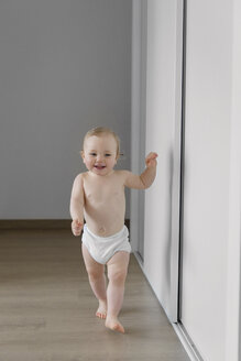Baby boy learning to walk in a corridor - LITF000177
