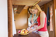 Two smiling young women standing in a caravan preparing fruits - HAPF000038
