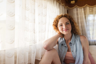 Portrait of smiling young woman sitting in a caravan - HAPF000041
