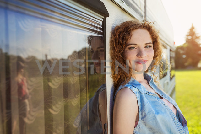 Portrait of smiling young woman leaning against caravan - HAPF000056