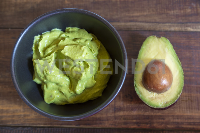 Bowl of guacamole and half of an avocado on wood - SARF002394