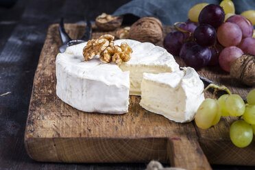 Wooden board with sliced camembert, walnuts and grapes - SBDF002575