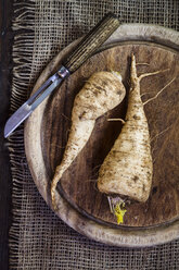 Parsley roots and peeler on wooden board and jute - SBDF002578